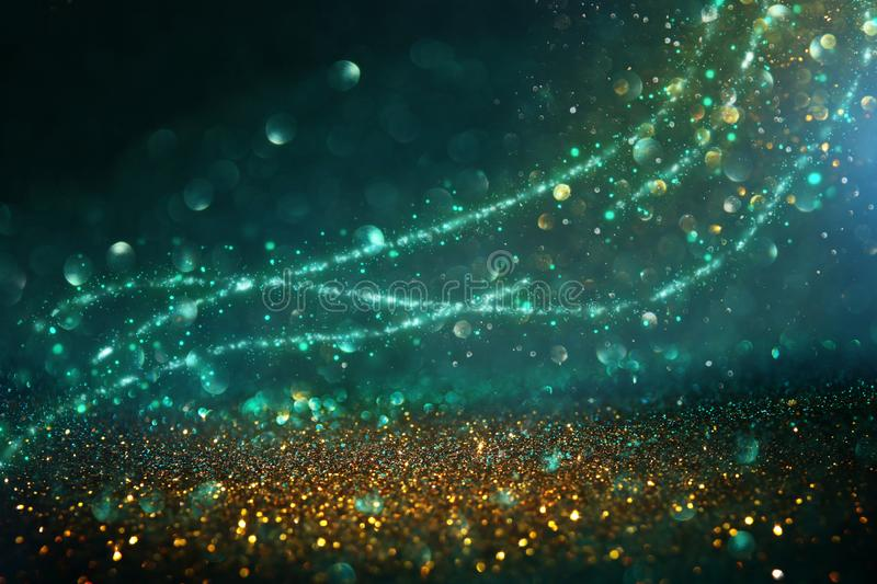 Abstract glitter lights background. black, blue, gold and green. de-focused royalty free stock photography