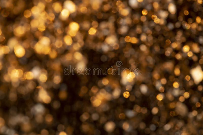 Abstract golden glitter blurred background and magical bokeh, looks like invitation for Christmas. Defocused photo. Wallpaper royalty free stock photography