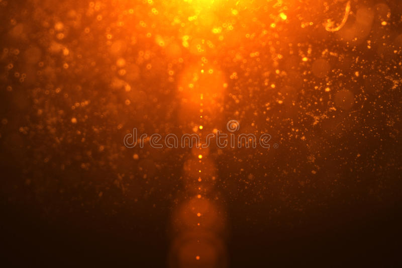 Abstract golden light flare leaks with gold particles. Bokeh stock photos