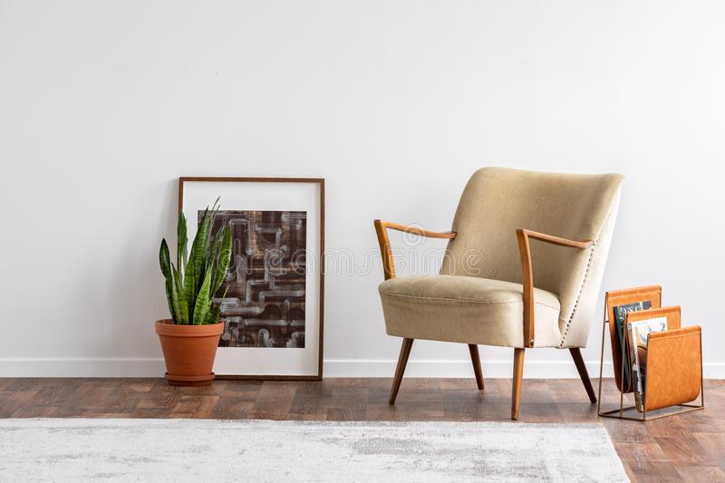 Abstract graphic in wooden frame next to green plant in ceramic pot and elegant beige armchair and orange magazine rack, real royalty free stock photos