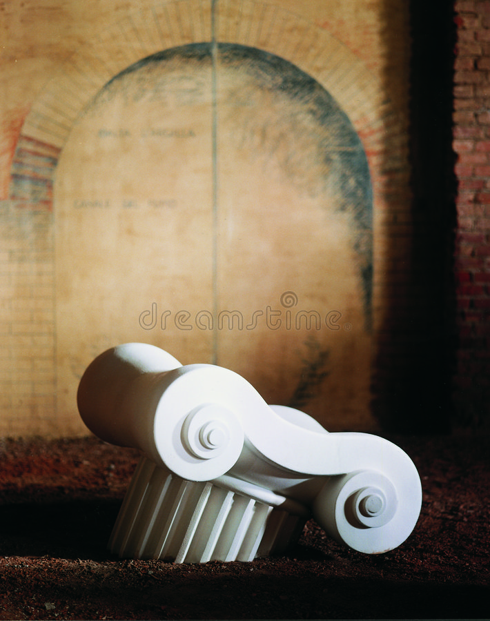 Abstract Greek column. An abstract rendering of a bright white Greek column piece half buried in the ground in front of an old brownish brick wall stock photography