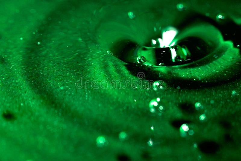 Abstract green background with water, drops and waves macro. Abstract green background with water, drops and waves close royalty free stock photography
