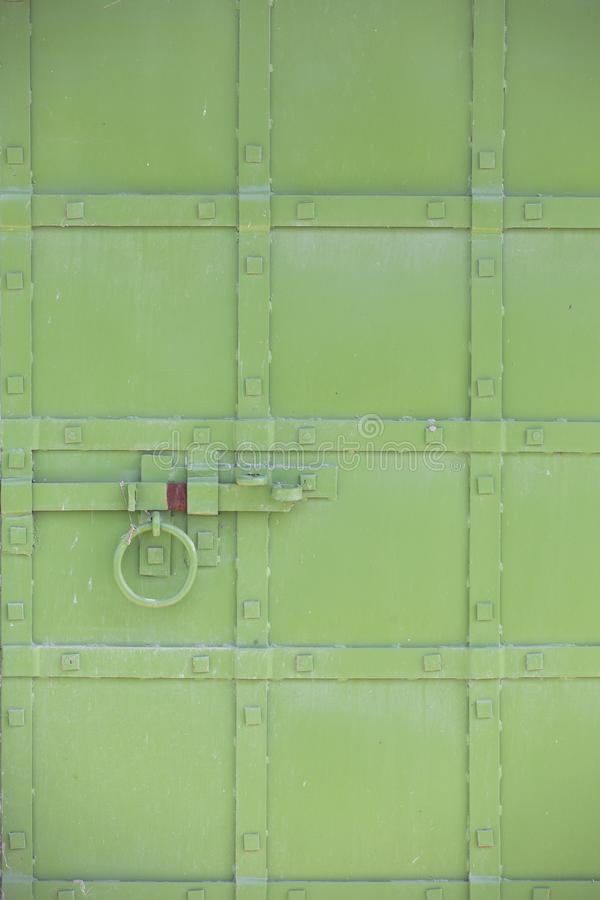Abstract green industrial metal background texture with bolts and rivets. Old painted metal background Can be used as a background. Close-up royalty free stock images