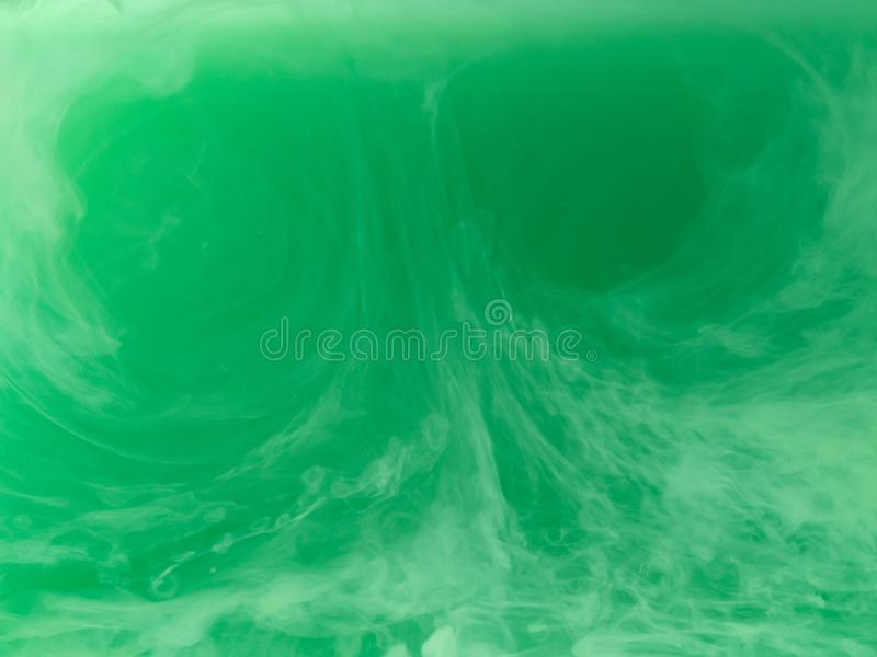 Abstract green pattern. Close up view. Blurred background. Acrylic paint dropped into liquid, abstract background. Ink. Waves in liquid. Acrylic smoke under stock photos