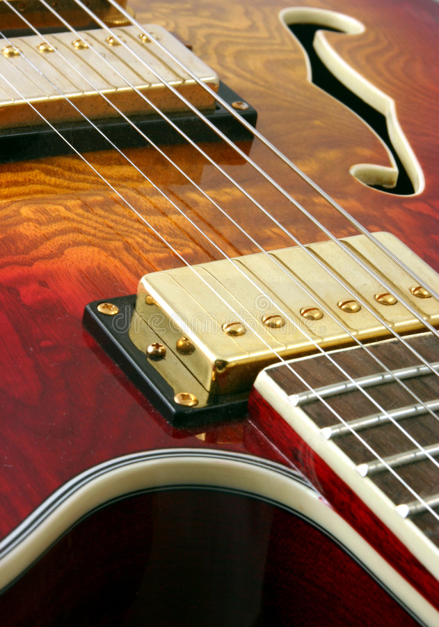 Abstract guitar close up. Macro shot looking down a semi accoustic jazz guitar showing wood grain and colour, strings pick ups sound holes and frets stock images