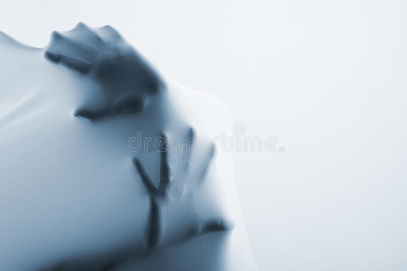 Abstract hands, human arm inside fabric. Studio shot toned blue over gray background royalty free stock photos