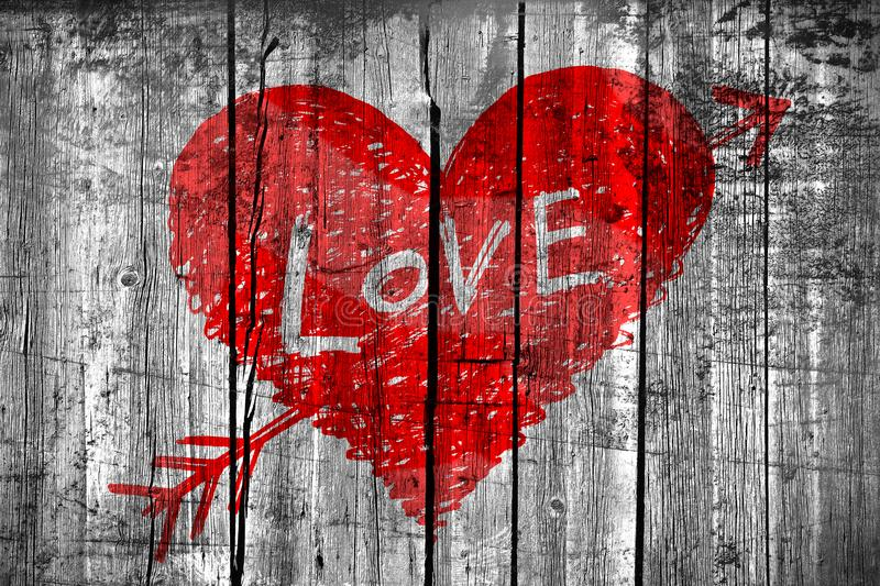 Abstract heart pierced by an arrow with word LOVE on grunge wooden wall stock photo