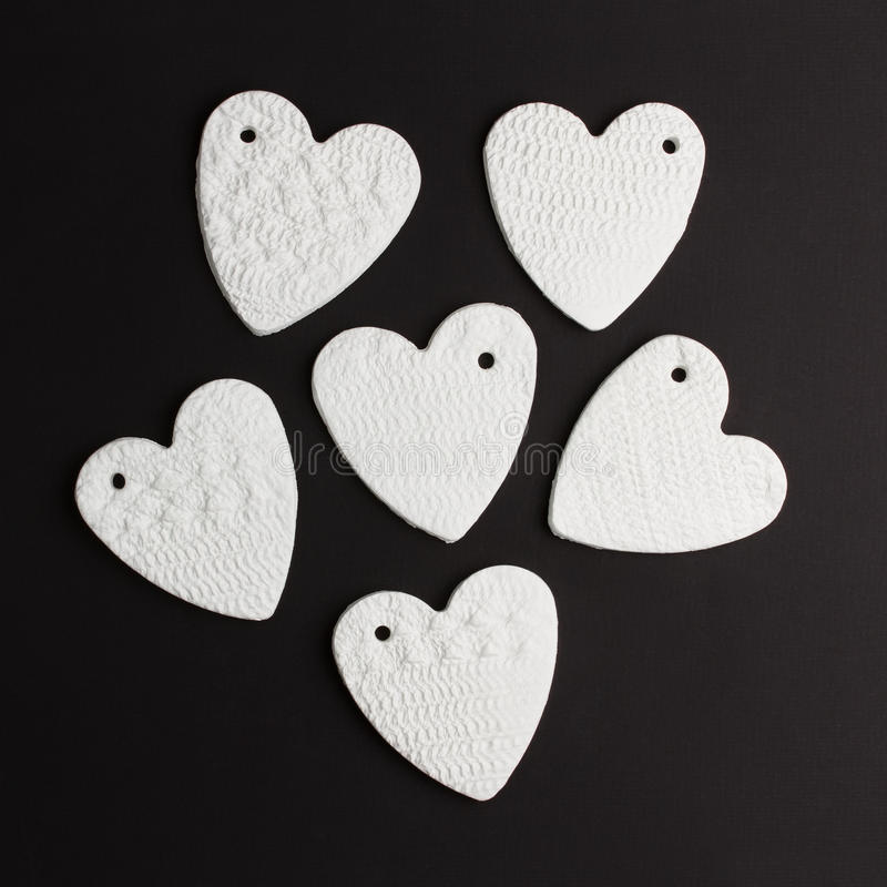 Abstract hearts. Made of from white China clay against black background stock photo
