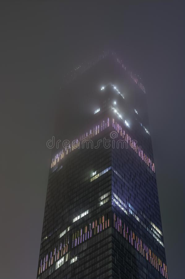 Abstract hi-tech background of fragment modern elevation office buildings of steel and glass with lights switched at night in the. Fog, Moscow, Russia royalty free stock photos