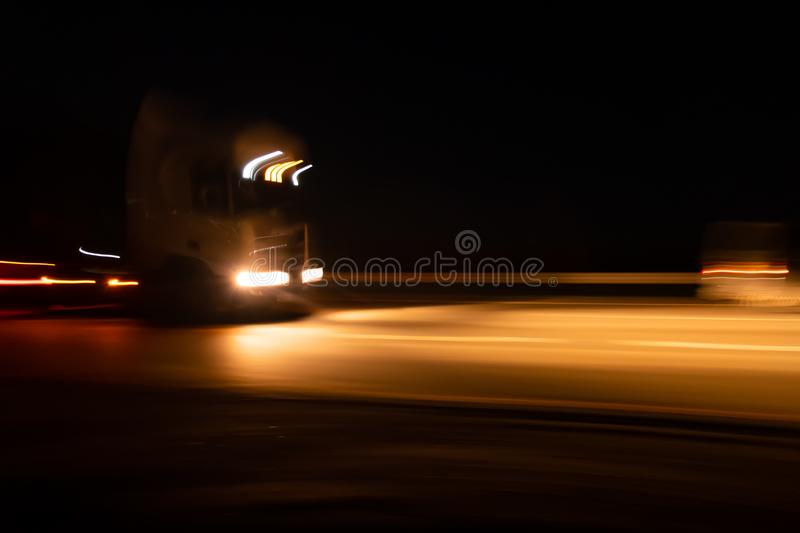 Abstract image with blurry car fragments on a speedway.The cars moves at fast speed at the night. Blurred lights with car on high royalty free stock photos