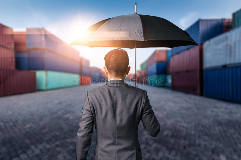 The abstract image of the Businessman is spreading umbrella during sunrise overlay with container yard image. The concept of trans royalty free stock photo