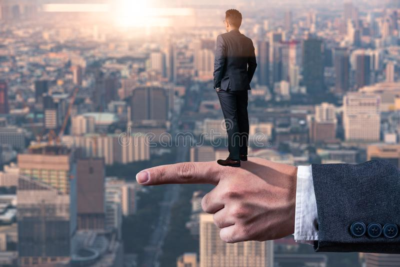 The abstract image of the businessman standing back on the finger during sunrise and looking forword. The concept of modern life, stock photography