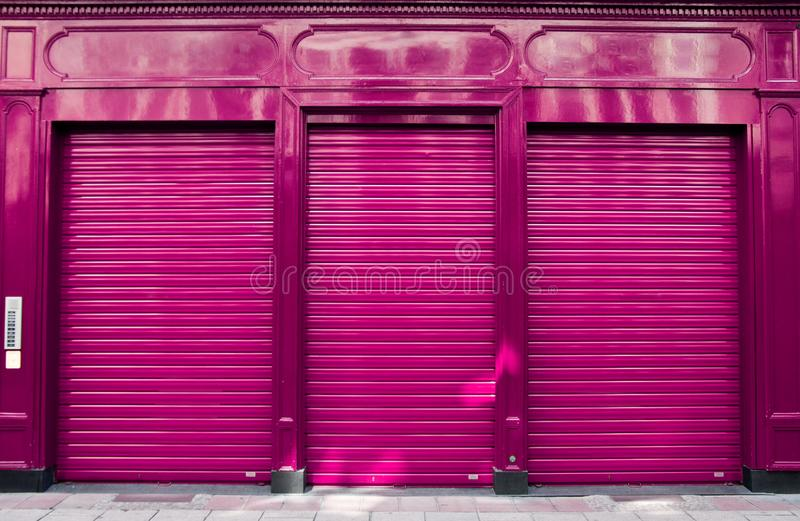 Business closure abstract with purple shop facade. Abstract image of a closed for business shop, facade of a retailer with horizontal blinds down royalty free stock images