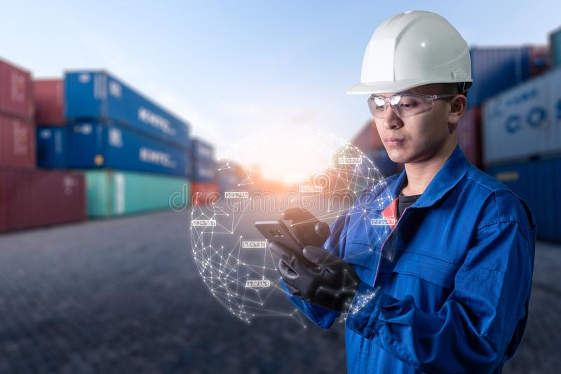 The abstract image of engineer point to the hologram on his smartphone and blurred container yard is backdrop. royalty free stock image