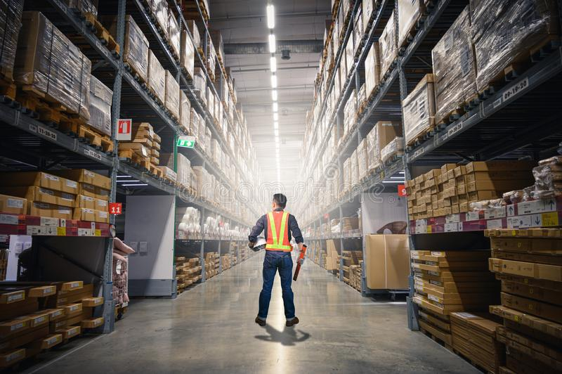 The abstract image of the engineer standing in front of the warehouse storage. the concept of engineering, shipping, management, w royalty free stock photo