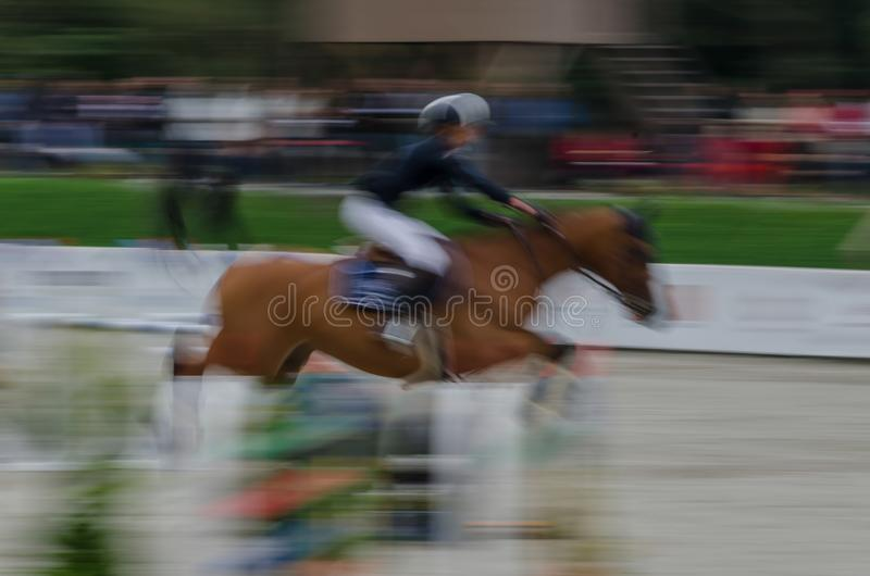 Abstract image with a horse at show jumping. Abstract image with a moving rider and horse at show jumping on blurred background, Herneacova, Romania royalty free stock image