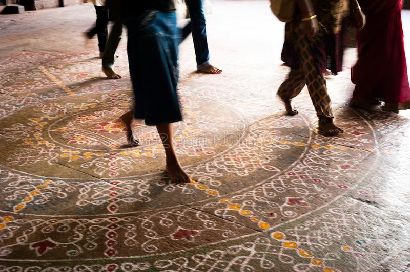Barefoot pilgrims walking on the floor with painted mandala  in Hindu temple. India stock image