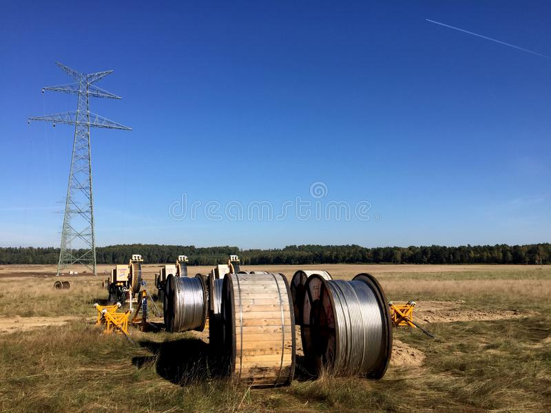 Power lines installation, new line being constructed. Abstract image of new power line being constructed, the cables on huge spools with pylon without cables in stock photo