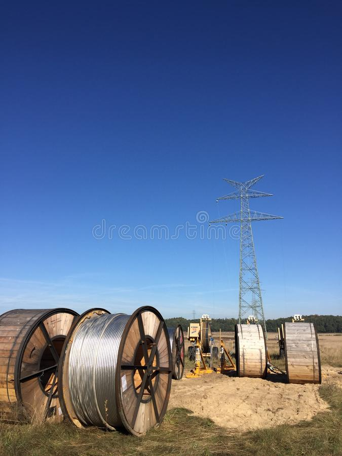 Power lines installation, new line being constructed. Abstract image of new power line being constructed, the cables on huge spools with pylon without cables in stock image