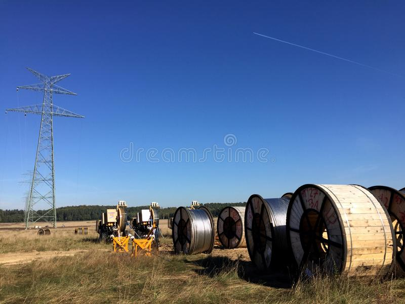 Power lines installation, new line being constructed. Abstract image of new power line being constructed, the cables on huge spools with pylon without cables in royalty free stock photos
