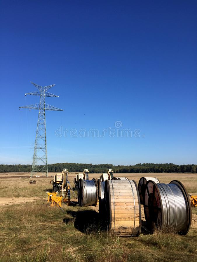 Power lines installation, new line being constructed. Abstract image of new power line being constructed, the cables on huge spools with pylon without cables in royalty free stock photo