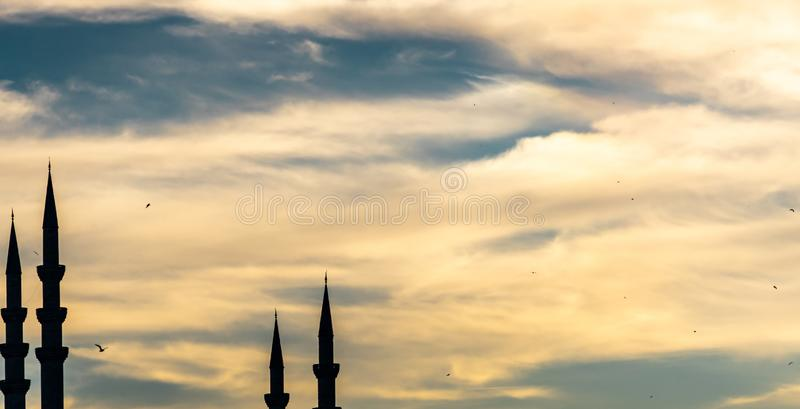 Abstract image of the shilouette of four minarets against a dramatic cloudy sky, artistic royalty free stock image