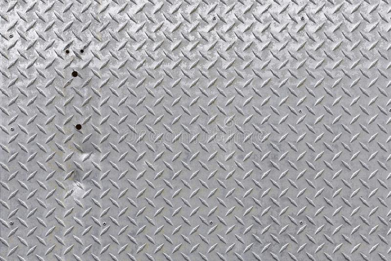Shiny Metal Floor Grate Texture. An abstract image of shiny metal industrial floor grate texture with a dent in it stock photo