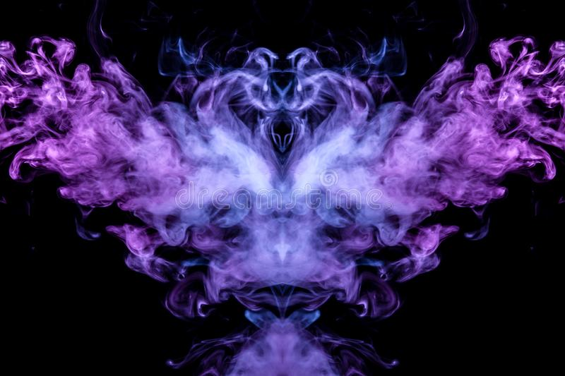 Abstract image of smoke of different colors in the form of horror or the bird with wings on a black isolated background. Soul and. Ghost in mystical shape stock images