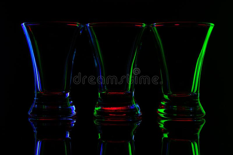 Abstract image of three empty shots with colored edges on black background. Cocktail glasses concept royalty free stock photo