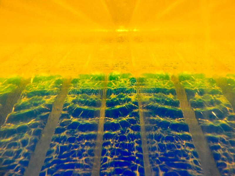 Abstract image of two fluids with different densities interacting with each other. Contains gold, blue, green colors, have. Perspective, selective focus stock photography