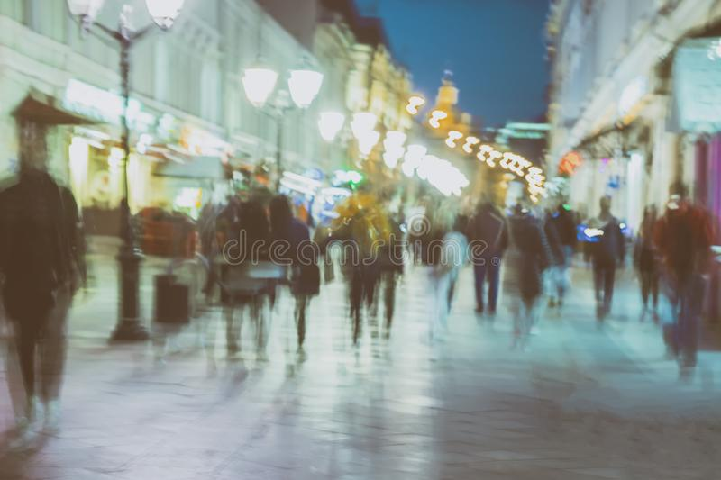 Abstract image of unrecognizable silhouettes of people walking in city street in evening, nightlife. Urban modern stock photography