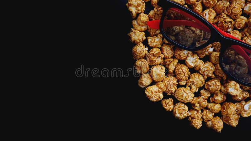 Abstract image of viewer, 3D glasses and popcorn on black background. Still life, top view, flat lay. Concept cinema and entertainment royalty free stock images