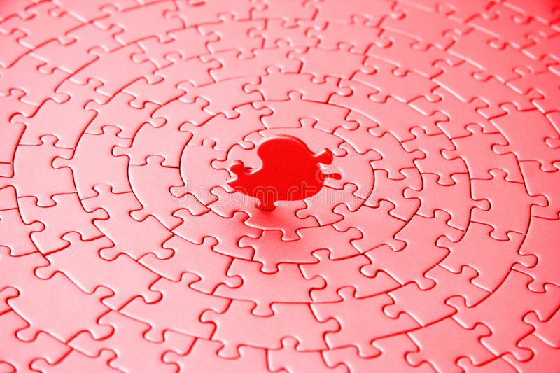 Abstract of a jigsaw in red and pink with the last piece upstanding. Pieces fitting together in form of a spiral - adobe RGB royalty free stock photo