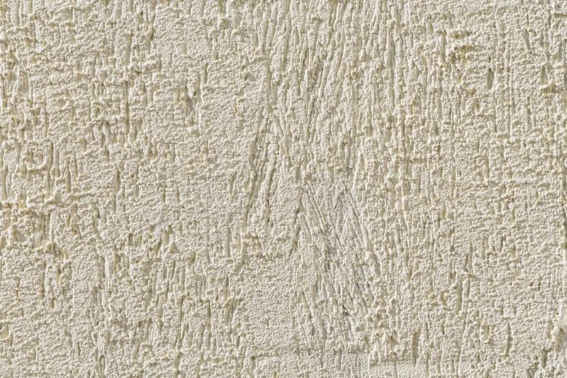 Abstract light beige grainy background with the texture of coarse grained new decorative plaster. Construction and repair. stock image