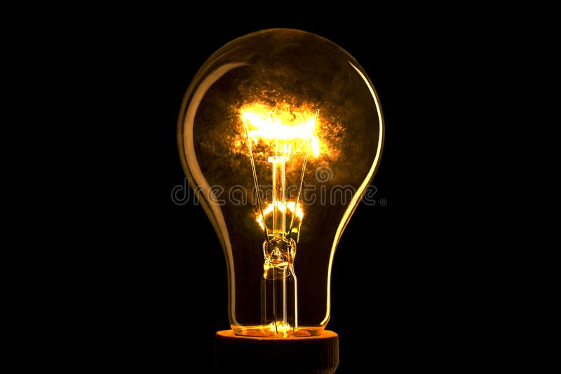 Abstract light bulb on the black background. Lamp light in the dark. Electric bulb. Glowing light in the dark. stock photos
