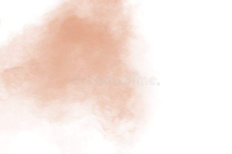 Abstract light orange powder explosion on white background. Freeze motion of light orange dust particles splash.  royalty free stock photography
