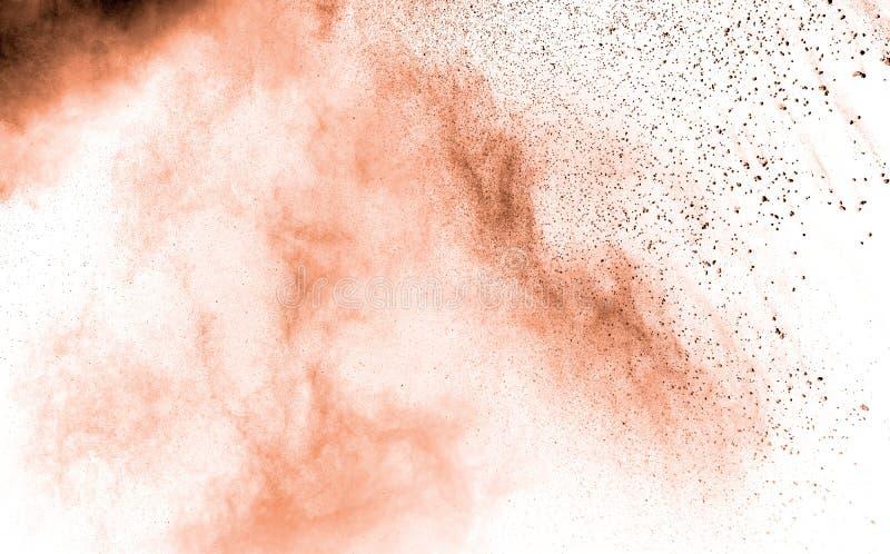 Abstract light orange powder explosion on white background. Freeze motion of light orange dust particles splash.  royalty free stock photos