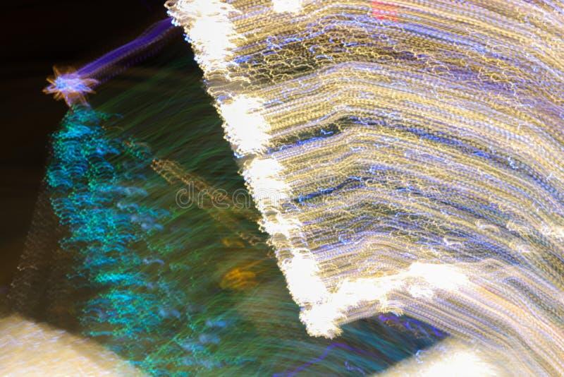Abstract long exposure photo of Christmas tree and street festive lights, city xmas tree defocused light motion at night stock photo