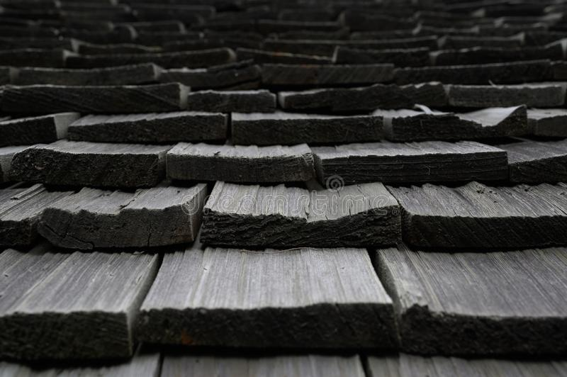 Abstract look of wood shingle roof tiles. Parallel but uneven pattern of old wood shingle roof tiles in close up shot royalty free stock photos