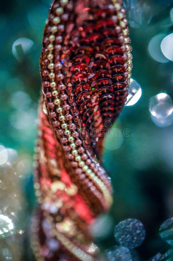 Abstract macro view of Christmas sequin glitter ornament, portrait view. Intentional selective focus for artistic effect. Abstract detail view of red and green royalty free stock image