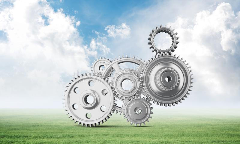 Abstract mechanism with cogwheels on green meadow. Construction and manufacturing. Mechanical technology machine engineering. Nature landscape with green grass stock images