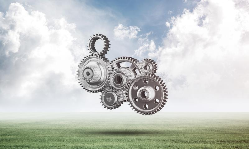 Abstract mechanism with cogwheels on green meadow. Construction and manufacturing. Mechanical technology machine engineering. Nature landscape with green grass royalty free stock image