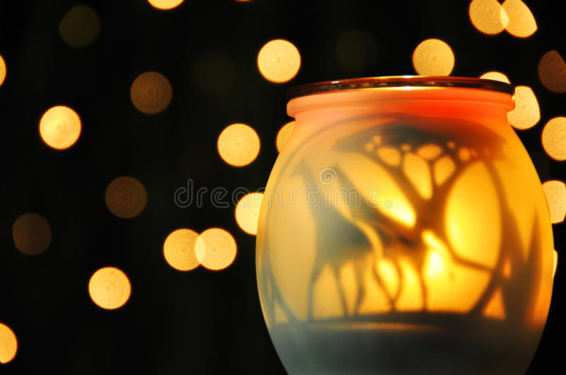 Abstract mellow yellow sparkling night lights. A soft glowing frosted glass candle globe gives off a moody, dreamy light with the twinkling fairy lights turning