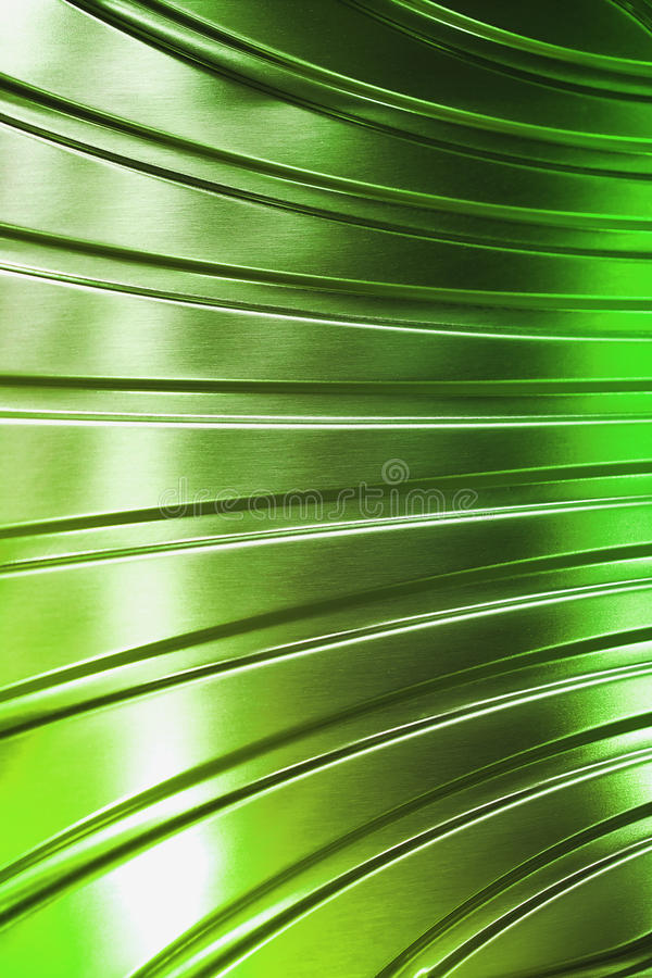 Abstract metal tube. Metal surface of curved plate in green light stock photography