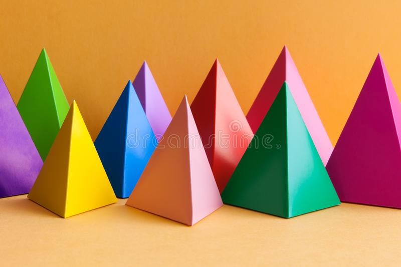 Abstract minimal geometric pattern background with prism pyramid triangle shape figures. Yellow blue pink green violet royalty free stock photo