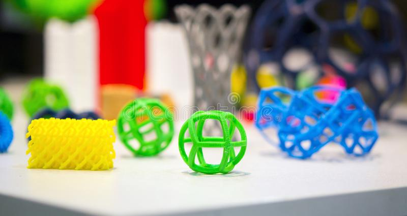 Abstract models printed by 3d printer close-up. Bright colorful objects printed on a 3d printer on a white table. Progressive modern additive technology stock image