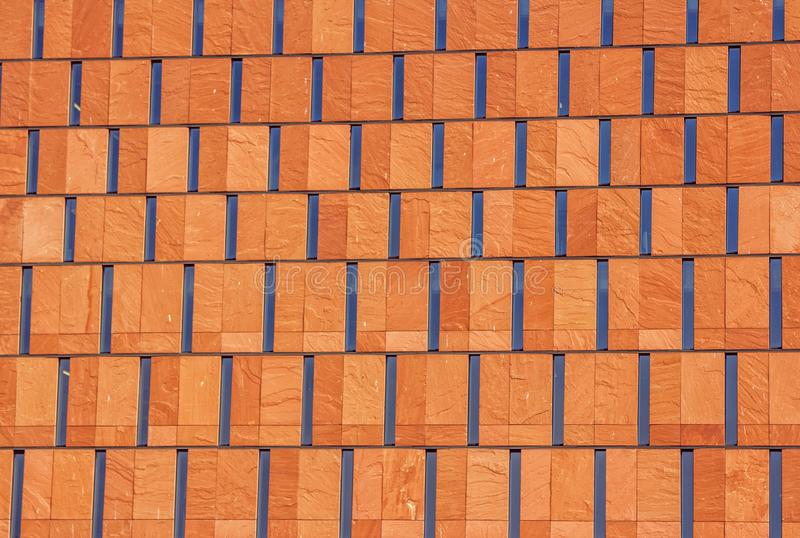 Abstract modern architectural background. Orange decorative tile and glass surface stock photo