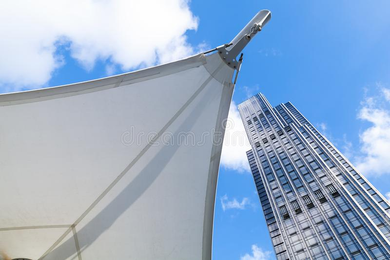 Tall office tower near awning in sails shape royalty free stock photos