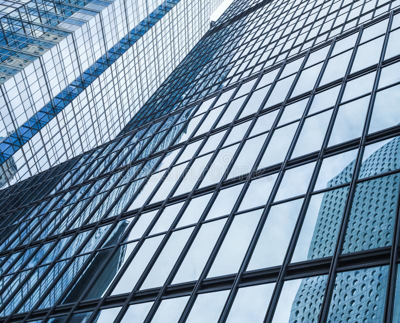 Abstract modern business architecture. Background, walls made of glass and steel with reflections of cloudy sky royalty free stock photo