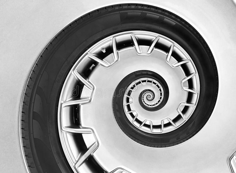 Abstract modern car wheel rim with tire twisted into surreal spiral. Automobile repetitive pattern background illustration. Car ab royalty free stock images